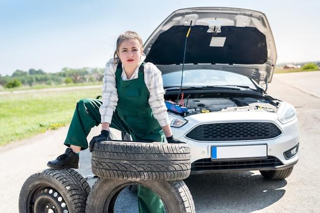 Mécanicien de femme posant avec roue de secours et pneus