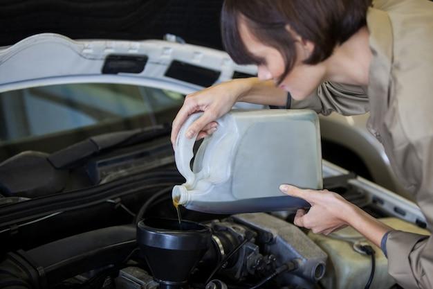 Mécanicien femme versant de l'huile lubrifiante dans le moteur de voiture
