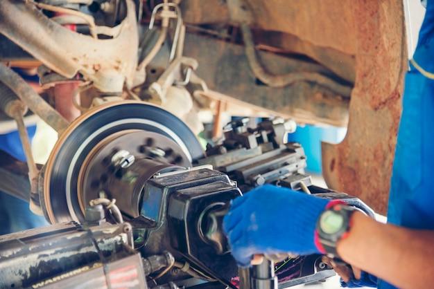 Mécanicien homme mains fixation voiture dans le centre de la voiture mobile automobile.