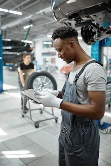 Mécanicien, homme, utilisation, ordinateur portable, dans, atelier mécanique