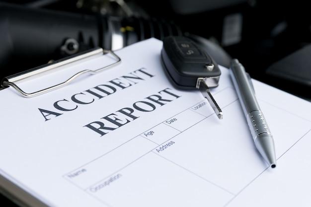 Mécanicien inspecter la voiture endommagée et remplir le formulaire de rapport d'accident
