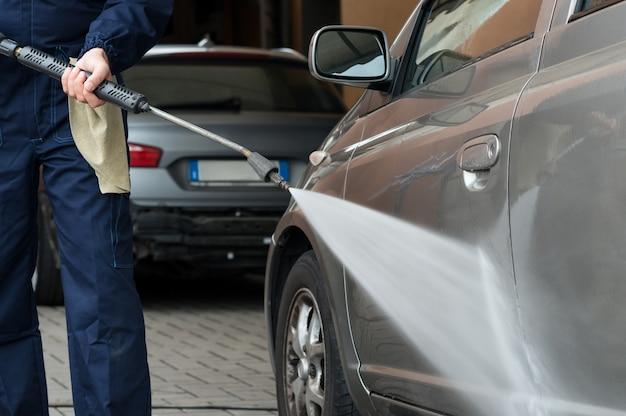Un mécanicien lave une voiture à l'eau sous pression