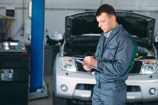Mécanicien de maintien de l'enregistrement de voiture sur le presse-papiers à l'atelier de réparation.