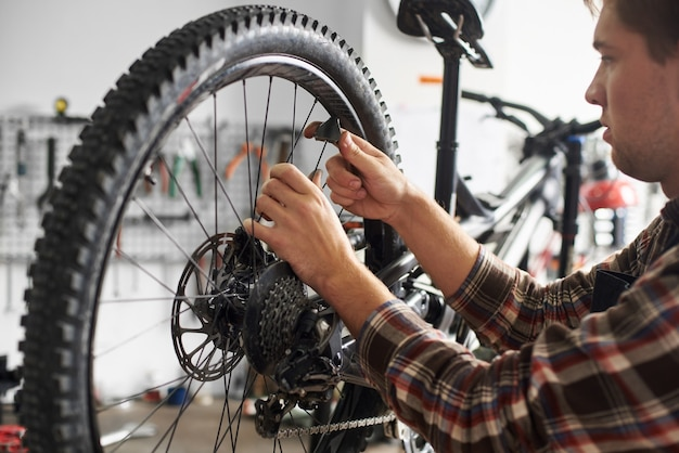 Mécanicien masculin faisant un service dans un atelier de réparation de vélos à l'aide d'outils