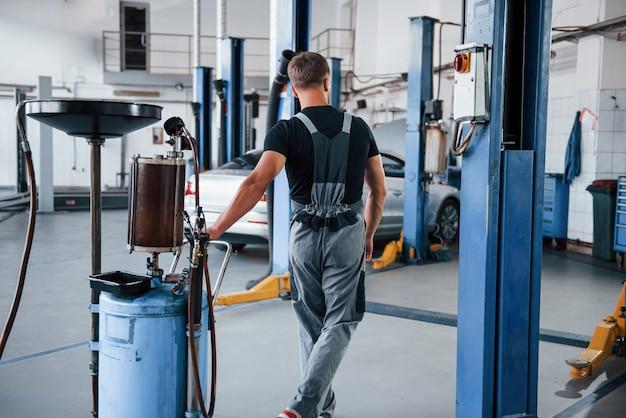 Mécanicien masculin utilise un appareil spécial pour réparer une automobile cassée dans un garage