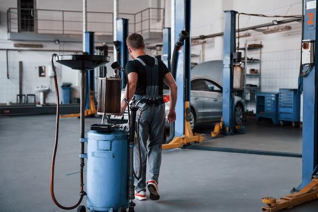 Mécanicien masculin utilise un appareil spécial pour réparer une automobile cassée