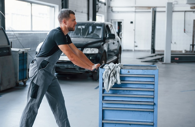 Mécanicien masculin utilise différents outils pour réparer une automobile cassée dans un garage