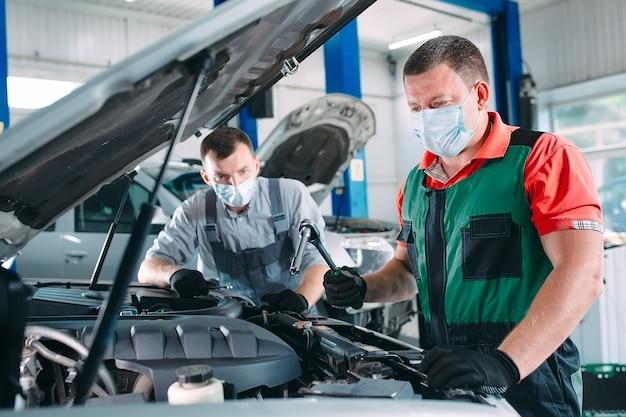 Un mécanicien masqué vérifie la voiture à la station-service