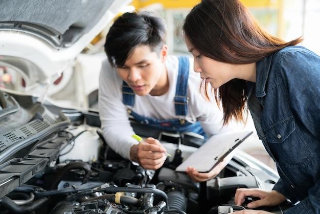 Mécanicien montrant la liste des services rendus à une cliente pendant qu'un homme travaille à l'arrière-plan.