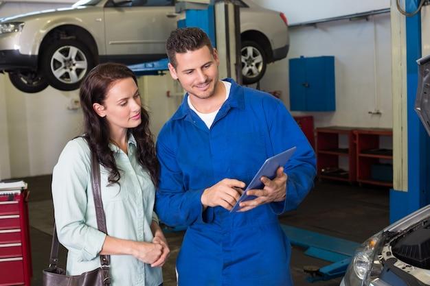 Mécanicien montrant le tablet pc au client