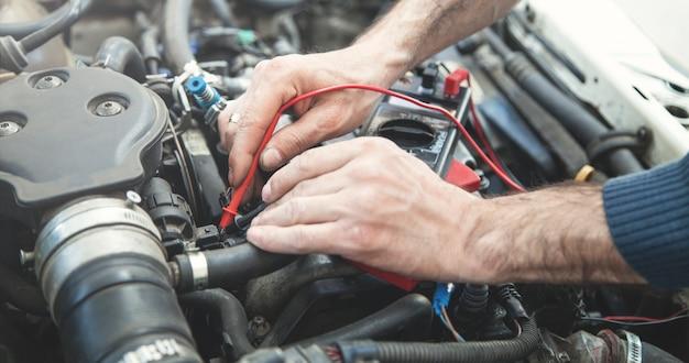 Mécanicien avec un moteur de voiture d'essai multimètre. service automobile