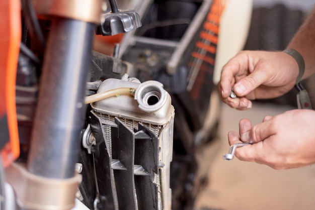 Mécanicien de moto, remplaçant le radiateur de refroidissement. remplacement ou entretien du radiateur.