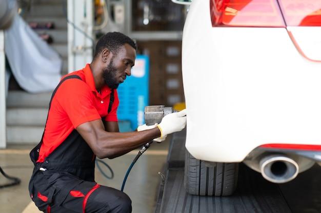 Mécanicien noir travaillant sous un véhicule dans une station-service de voiture