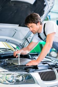 Mécanicien avec outil de diagnostic dans l'atelier de voiture