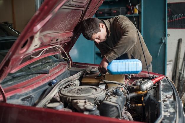 Mécanicien ouvrier verser de l'antigel dans le système de refroidissement