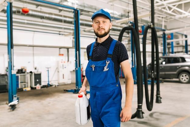 Mécanicien avec un pétrolier dans un atelier automobile