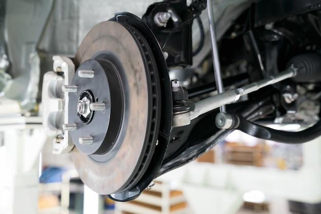 Mécanicien pièces automobiles tout en travaillant sous une auto levée