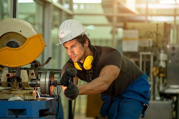 Mécanicien portant une sécurité uniforme dans le métal de tour de machine de travail en usine, concept de l'industrie.