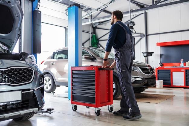 Mécanicien poussant la boîte avec des outils et se préparant à résoudre un problème de voiture en marchant dans un salon de voiture.