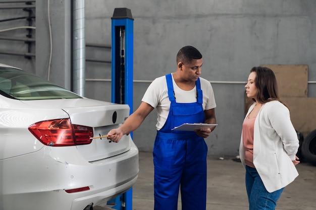 Mécanicien avec presse-papiers discute de la réparation automobile avec une femme
