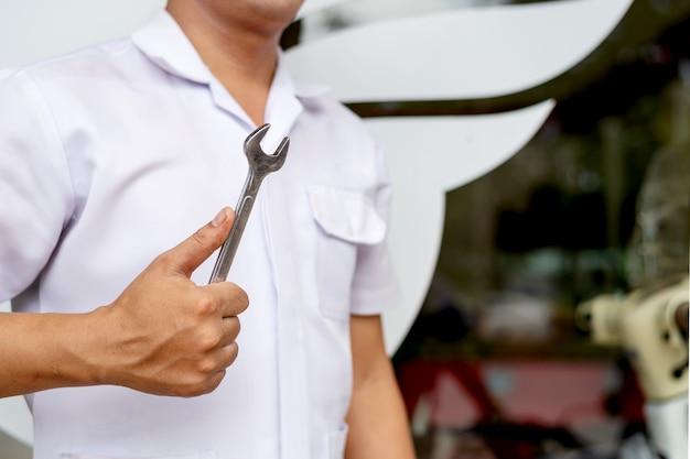 Mécanicien professionnel homme en uniforme tenant une clé