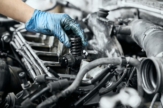 Mécanicien professionnel vérifiant la buse dans le moteur de voiture diesel