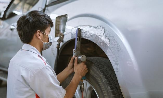 Mécanicien réparant la carrosserie et la peinture avec un service professionnel