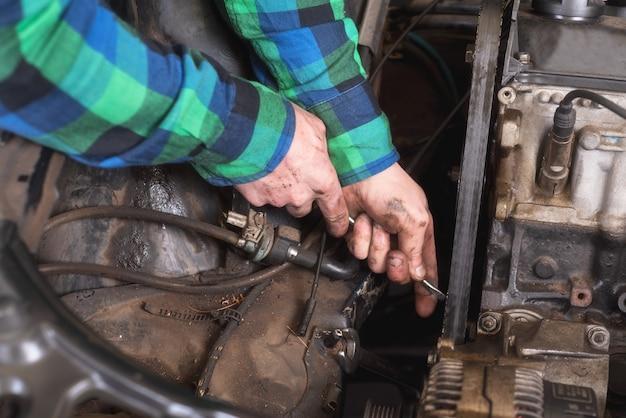 Mécanicien réparant le moteur. vérification de la ceinture auxiliaire.