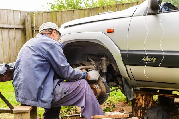Mécanicien réparant la suspension avant d'une voiture