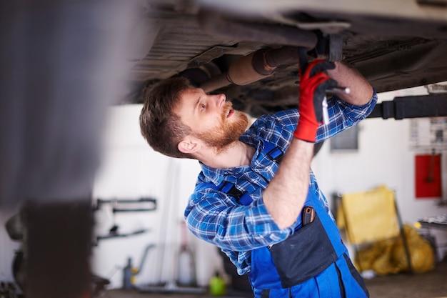 Mécanicien réparant une voiture dans l'atelier