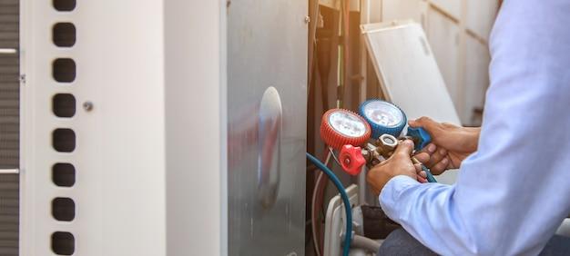 Mécanicien en réparation d'air utilisant un équipement de mesure pour le remplissage de climatiseurs industriels.