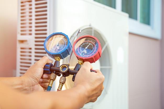 Mécanicien de réparation d'air utilisant un équipement de mesure de pression pour remplir le climatiseur domestique