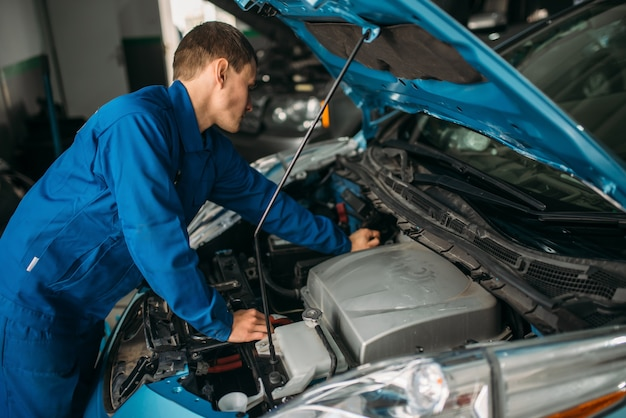 Mécanicien répare le moteur de la voiture, le diagnostic du moteur.
