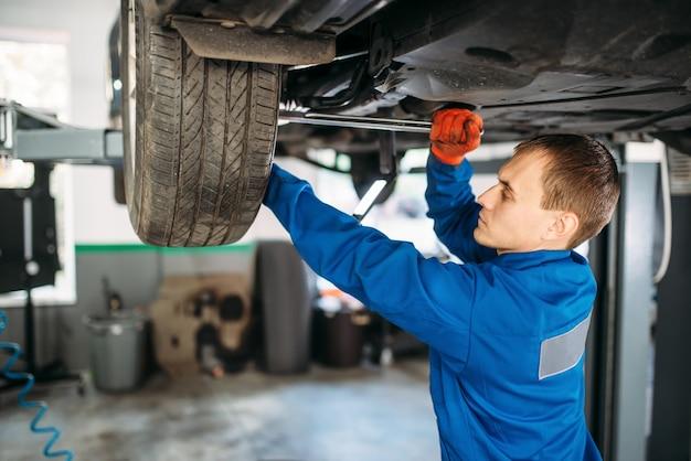 Mécanicien répare la suspension, voiture sur l'ascenseur