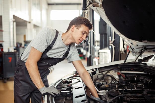 Un mécanicien répare une voiture dans un service automobile et entretient des véhicules.