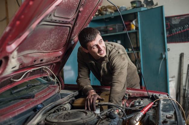 Mécanicien de service automobile travaillant dans une voiture sous le capot