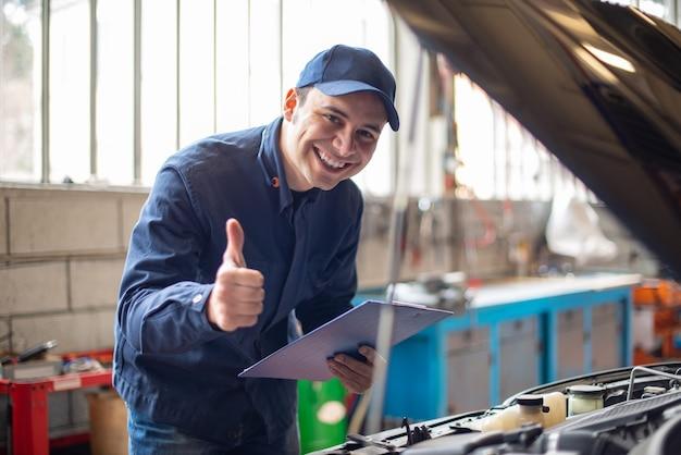 Mécanicien souriant donnant un coup de pouce devant une voiture avec le capot ouvert
