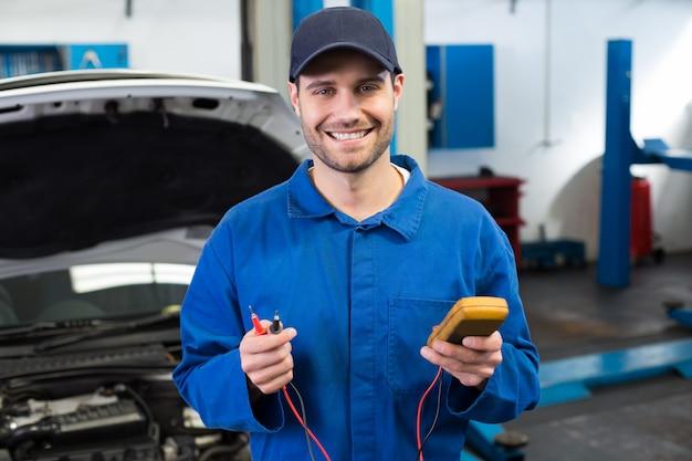 Mécanicien souriant à l'outil de prise de vue