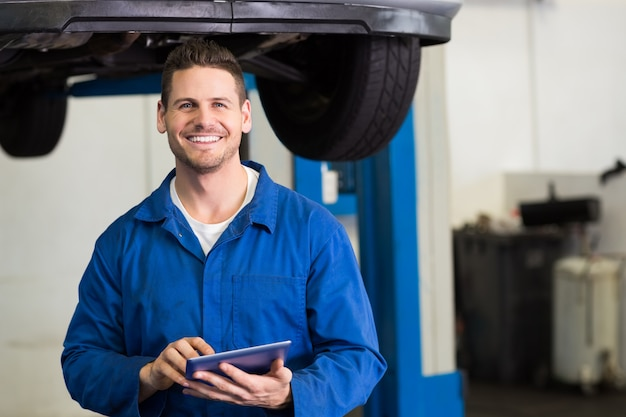 Mécanicien souriant en regardant la caméra à l'aide d'une tablette au garage de réparation