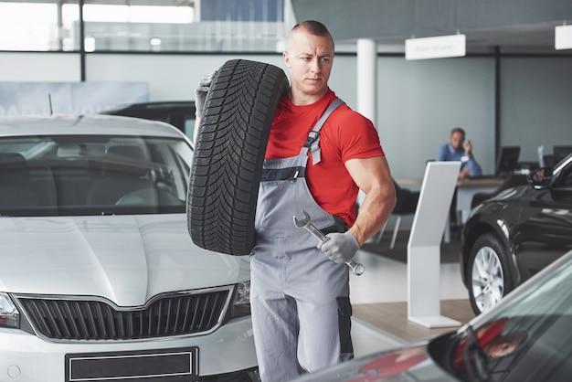 Mécanicien tenant un pneu au garage de réparation. remplacement des pneus d'hiver et d'été.