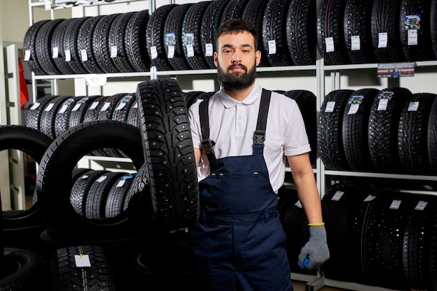 Mécanicien tenant un pneu et montrant les pneus de roue au service de réparation automobile et magasin de magasin automobile, jeune homme barbu en uniforme travaillant dans un garage de réparation automobile