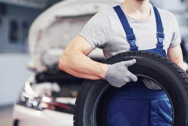 Mécanicien tenant un pneu de pneu au garage de réparation. remplacement des pneus hiver et été
