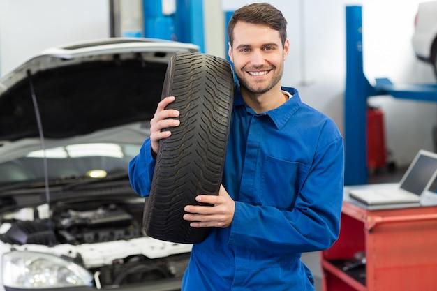 Mécanicien tenant une roue de pneu