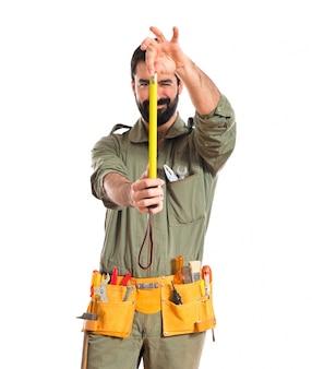 Mécanicien tenant un ruban à mesurer
