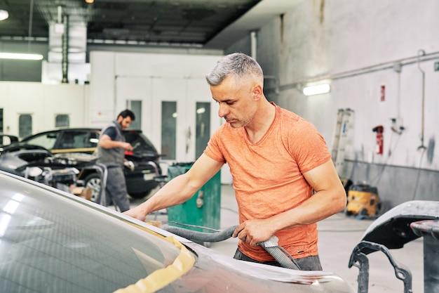 Un mécanicien en train de polir une voiture de sport