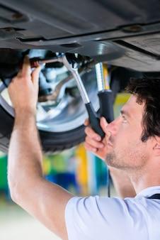 Mécanicien travaillant dans un atelier automobile sur une roue
