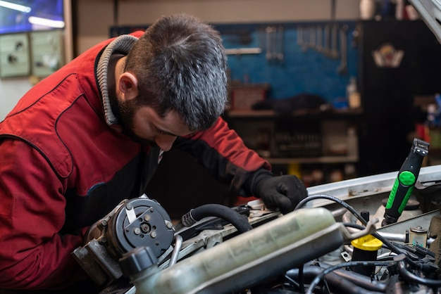Mécanicien travaillant sur le moteur dans l'atelier