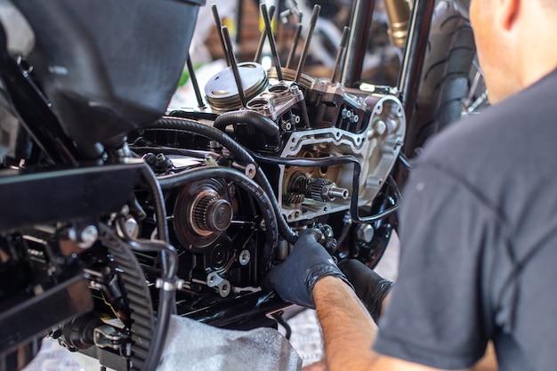 Mécanicien travaillant sur la réparation d'une moto dans l'atelier