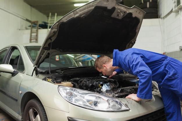Mécanicien travaillant sous le capot de la voiture