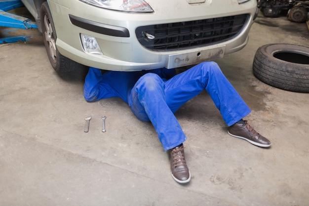 Mécanicien travaillant sous la voiture dans le garage